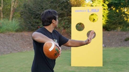 Man throwing football through holes