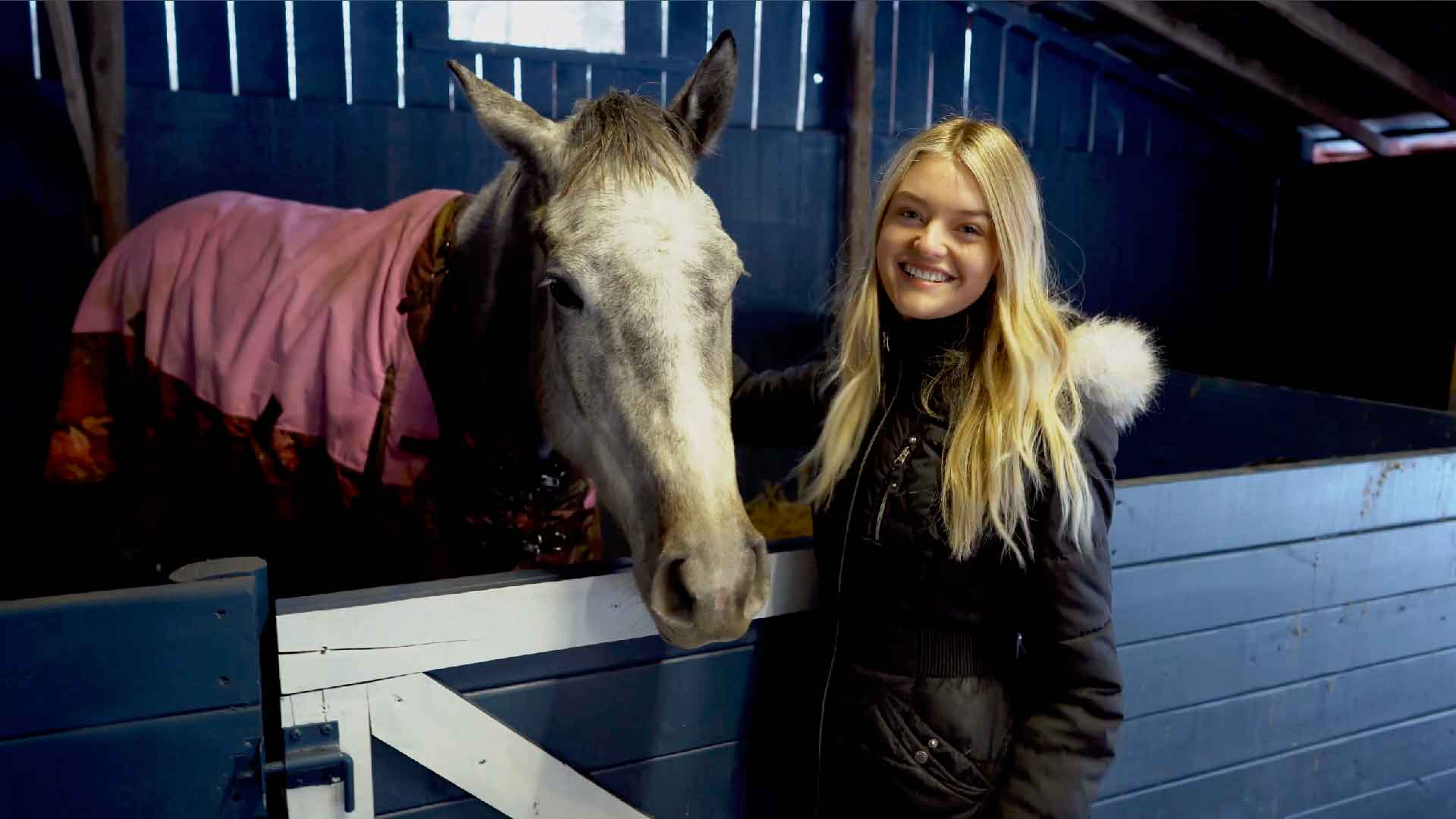 Willow standing next to a stall with one of her horses.