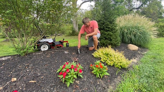 Man in a garden bed planting bulbs